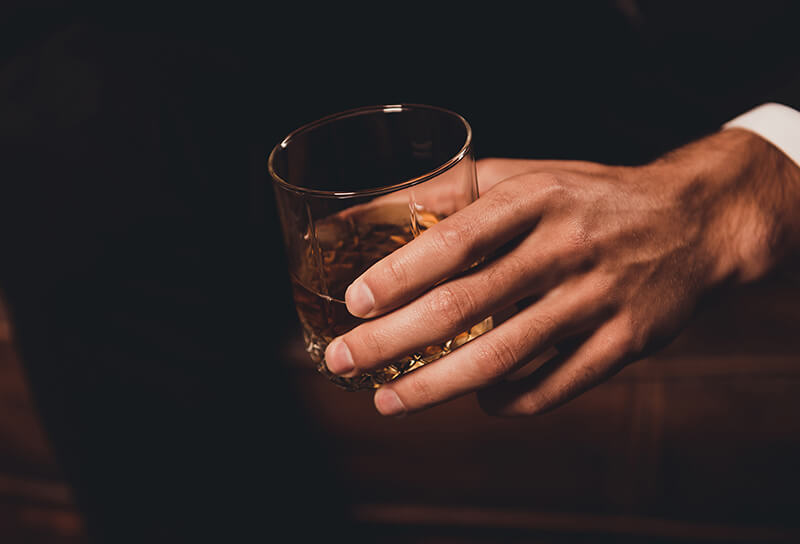 man's hand holding a glass